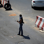 A local resident takes guard at a checkpoint in Gargaresh neighborhood, central Tripoli.