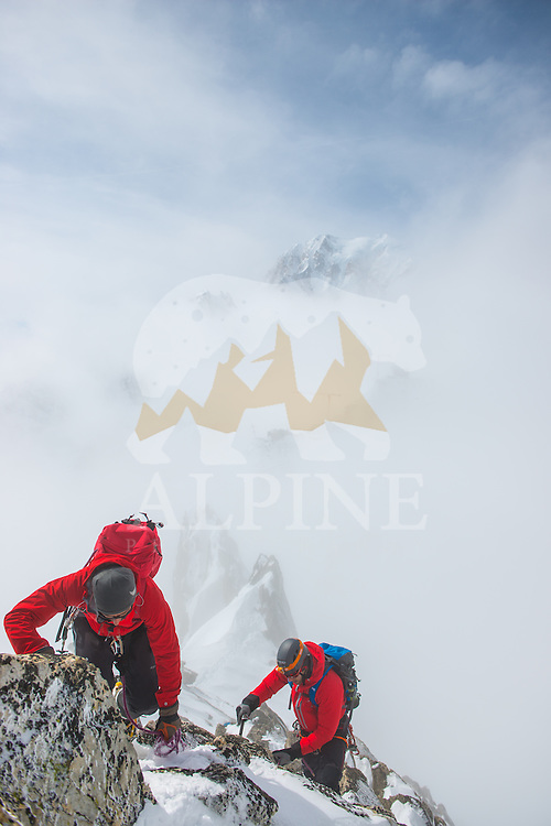 A pair of mountaineers as seen during the traverse of a rock feature on a ridge of Aiguilles Marbrées on a cold and cloudy Winter day in Mont Blanc Massif. In the background the iconic south face of Mont Blanc.