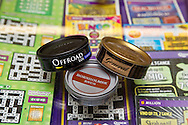 Tins with snus, tobacco for oral use, at the desk in a Danish kiosk. From left the Danish products Offroad and Bornholmsk Snus. On the left the Swedish product General Snus. All boxes contain loose snus, Portion snus is not allowed in Denmark. PHOTO: ERIK LUNTANG / INSPIRIT Photo.