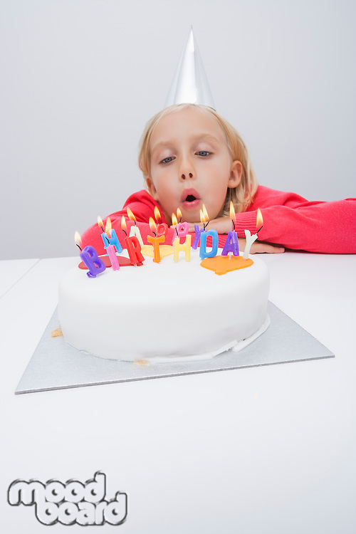 Girl blowing candles on birthday cake at table in house