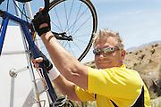 Man Putting His Bicycle into a Car Rack