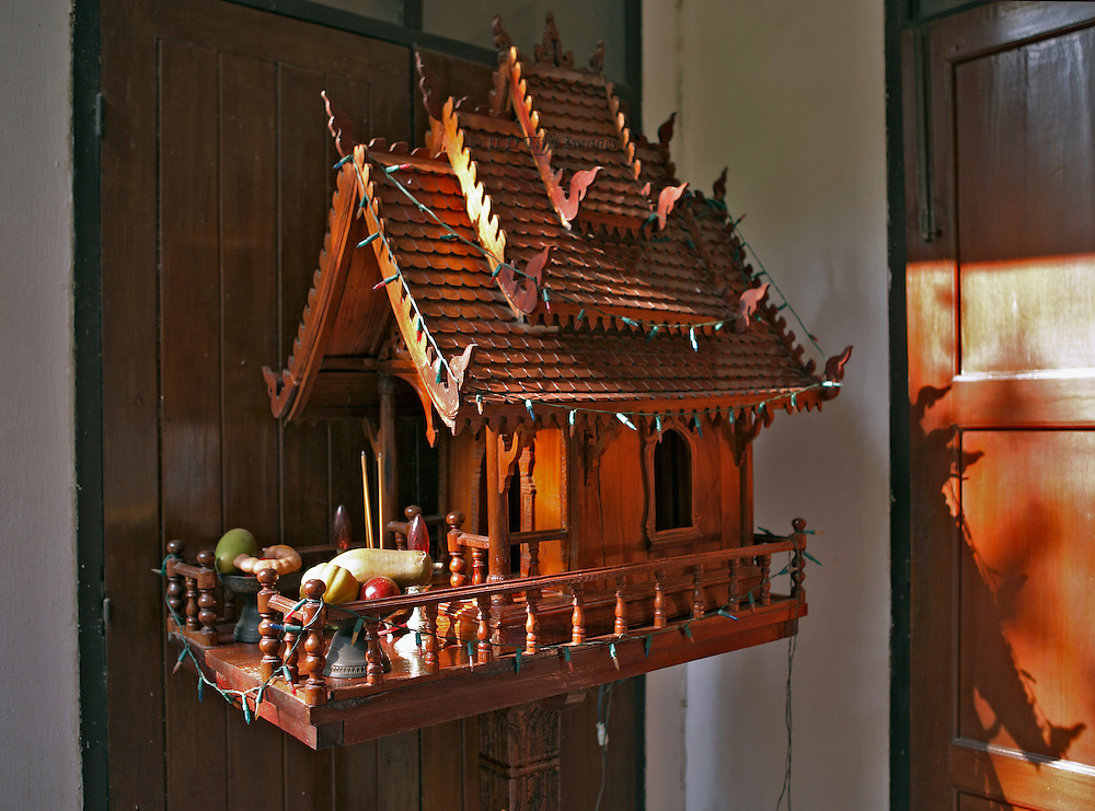 Fairly elaborate wooden spirit house on its pole just outside a guest house in the capital city of Laos.  The spirit house has multiple flying roofs and a front veranda filled with food offerings.  The whole is festooned with fairy light, unlit in the late afternoon sun but lit at dark.
