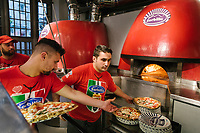 "NAPLES, ITALY - 8 DECEMBER 2017: A waiter picks up freshly baked pizzas by the wood-fired oven at Pizzeria Gino Sorbillo in Naples, Italy, on December 8th 2017.<br /> <br /> On Thursday December 7th 2017, UNESCO added the art of Neapolitan ""Pizzaiuolo"" to its list of Intangible Cultural Heritage of Humanity.<br /> <br /> The art of the Neapolitan 'Pizzaiuolo' is a culinary practice comprising four different phases relating to the preparation of the dough and its baking in a wood-fired oven, involving a rotatory movement by the baker. The element originates in Naples, the capital of the Campania Region, where about 3,000 Pizzaiuoli now live and perform. Pizzaiuoli are a living link for the communities concerned. There are three primary categories of bearers – the Master Pizzaiuolo, the Pizzaiuolo and the baker – as well as the families in Naples who reproduce the art in their own homes. The element fosters social gatherings and intergenerational exchange, and assumes a character of the spectacular, with the Pizzaiuolo at the centre of their 'bottega' sharing their art.<br /> <br /> In Naples, pizza makers celebrated the victory by giving away free pizzas."