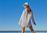Female Model in a Men's White Shirt Wearing a Fedora Hat On at the Beach