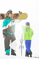 Full length of young men with snowboards in snow