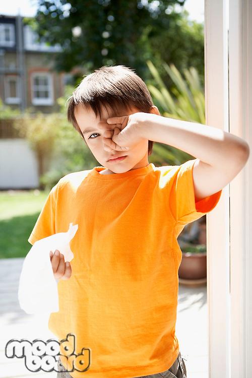 Boy with cold in backyard rubbing eyes