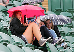 Tennis fans huddle under their umbrellas as they wait for the Laura Robson match to start as  rain stopped play for the first time this year at the Wimbledon Tennis Championships, Thursday, 27th June 2013<br /> Picture by Stephen Lock / i-Images