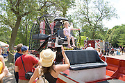 Mom waving to daughter age 6 on seat of fire department water rescue airboat. Aquatennial Beach Bash Minneapolis Minnesota USA