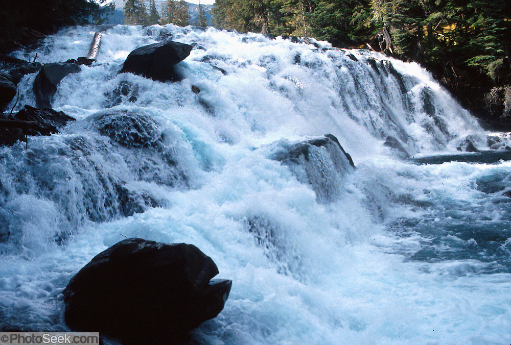 Water cascades in a whitewater falls in Bowron Lake Provincial Park, British Columbia, Canada. On the 73-mile Bowron canoeing trip, paddle a rectangular circuit of wilderness lakes and portage your canoe rolled on wheels. The Cariboo Mountains are the northernmost subrange of the Columbia Mountains.