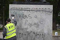 "© Licensed to London News Pictures. 08/06/2020. London, UK. Cleaners remove Graffiti from a statue of former British Prime Minister Winston Churchill in Parliament Square, after it was graffitied with the words ""was a racist"" during a Black Lives Matter demonstration In central London. The death of George Floyd, who died after being restrained by a police officer In Minneapolis, Minnesota, caused widespread rioting and looting across the USA. Photo credit: Ben Cawthra/LNP"