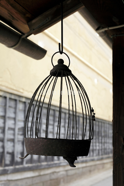 empty old metal bird cage hanging outside