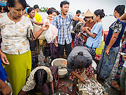 08 NOVEMBER 2014 - SITTWE, RAKHINE, MYANMAR:  A man auctions fresh fish brought into the pier in Sittwe. Fish are auctioned off as they are brought onto the pier. Sittwe is a small town in the Myanmar state of Rakhine, on the Bay of Bengal.  PHOTO BY JACK KURTZ