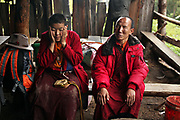 Two pilgrims, a nun and an old monk, stop out of the rain returning from Shenpu, Yunnan, China; September, 2013.