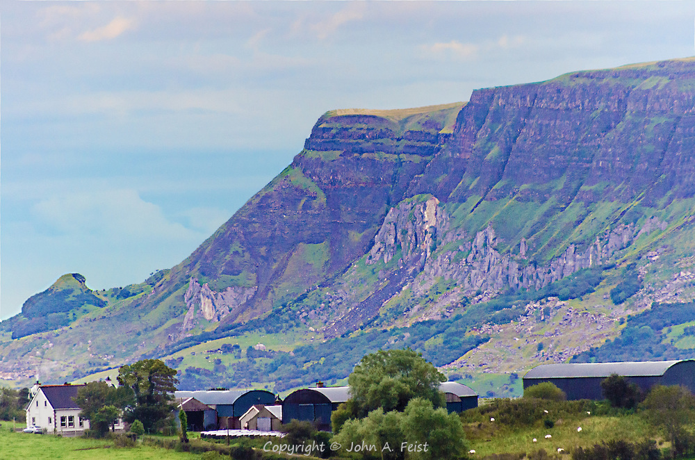 Looking up at the cliffs in Cushendall, county Antrim, Northern Ireland.  THose little white dots in the foreground are sheep grazing.  This is a beautiful part of the country.