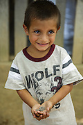 A boy holds two US quarters at the primary school in the town of Coyolito, Honduras on Wednesday April 24, 2013.