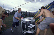 A band transport their gear into a tent at a festival, U.K, 1990s.