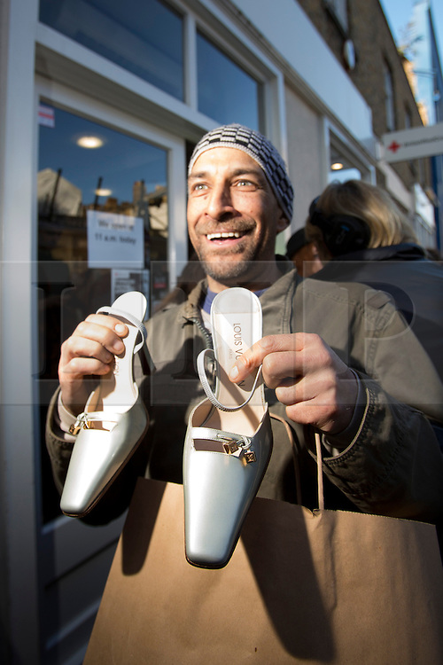 © licensed to London News Pictures. London, UK 22/11/2013. A man celebrating after buying a pair of shoes donated by Victoria Beckham to help raise money for Philippine typhoon disaster at the British Red Cross branch in Chelsea, London. Photo credit: Tolga Akmen/LNP