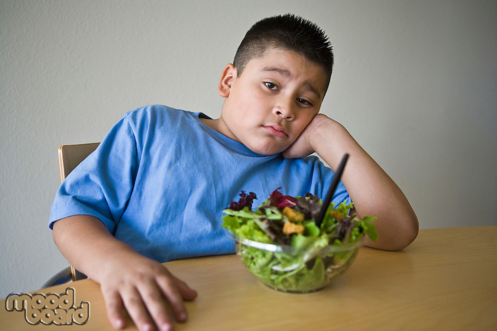 Pre-teen (10-12) boy sitting at desk with salad