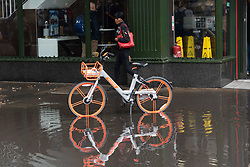 November 1, 2018 - London, London, UK - London, UK. People walk past a bike parked in a deep rain puddle after heavy rainfall hit London at lunchtime. Photo. credit: Ray Tang/LNP (Credit Image: © Ray Tang/London News Pictures via ZUMA Wire)