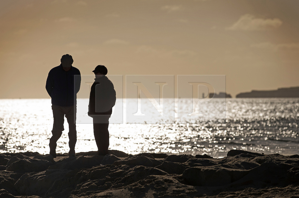 © Licensed to London News Pictures. 28/01/2016. Sandbanks, UK. Walkers take a stroll in the sunshine at Sandbanks in Dorset. Parts of the UK are enjoying a spell of sunshine after days of storms. Photo credit: Peter Macdiarmid/LNP