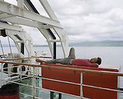 A Papua-bound KM Nggapulu passengers sleep on a box contains of inflatable liferafts. Althought most of the time its vessel sail in overcapacity, Pelni has maintained a good safety record with no major accident occured since early 80s.<br /> <br /> Indonesia&rsquo;s Pelni is the last great true passenger liners company in the world. It is the only company of its size that still serves scheduled vessels transporting people across various destination. In a far-flung archipelago nation, where many of the islands have no airport and most of its area made up of water, it is one important mean of transportation&mdash;and simply one of the best way to travel. One of Pelni's furthest regular route starts from Surabaya in East Java and ends in Papuan city of Merauke, basically the eastern end of Indonesia. The round trip voyage takes one month, passing more than two dozen ports and covering a distance of more than 8,000 kilometers.