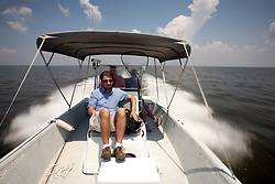 28 May 2010. Barataria Bay to Grand Isle, Jefferson/Lafourche Parish, Louisiana. <br /> Sunday Telepgraph reporter Philip Sherwell covers the BP oil spill story from a boat on  Barataria Bay. The ecological and economic impact are devastating to the region. Oil from the Deepwater Horizon catastrophe is evading booms laid out to stop it thanks in part to the dispersants which means the oil travels at every depth of the Gulf and washes ashore wherever the current carries it. The Louisiana wetlands produce over 30% of America's seafood and are the most fertile of their kind in the world.<br /> Photo credit; Charlie Varley<br /> www.varleypix.com