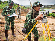 16 SEPTEMBER 2014 - SANGKHLA BURI, KANCHANABURI, THAILAND: Thai soldiers survey the area around the Mon Bridge, in the background. The 2800 foot long (850 meters) Saphan Mon (Mon Bridge) spans the Song Kalia River. It is reportedly second longest wooden bridge in the world. The bridge was severely damaged during heavy rainfall in July 2013 when its 230 foot middle section  (70 meters) collapsed during flooding. Officially known as Uttamanusorn Bridge, the bridge has been used by people in Sangkhla Buri (also known as Sangkhlaburi) for 20 years. The bridge was was conceived by Luang Pho Uttama, the late abbot of of Wat Wang Wiwekaram, and was built by hand by Mon refugees from Myanmar (then Burma). The wooden bridge is one of the leading tourist attractions in Kanchanaburi province. The loss of the bridge has hurt the economy of the Mon community opposite Sangkhla Buri. The repair has taken far longer than expected. Thai Prime Minister General Prayuth Chan-ocha ordered an engineer unit of the Royal Thai Army to help the local Mon population repair the bridge. Local people said they hope the bridge is repaired by the end November, which is when the tourist season starts.    PHOTO BY JACK KURTZ