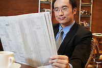 China Businessman reading newspaper at cafe table close-up