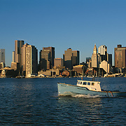 Boston Massachusetts USA skyline Harbor at sunrise, view from East Boston with fishing boat heading out to Atlantic Ocean fishing grounds
