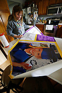 Rachel Gowey's mother, Rhonda Gowey, opens up a banner she had printed for Rachel's graduation party Thursday, May 12, 2016, as Rachel makes a brief stop at home in Urbandale before heading to her second gymnastics practice of the day. Rhonda Gowey credits Rachel's counselors and teachers for being flexible and making it possible for her daughter to graduate from public school, even with her demanding practice schedule.