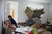 "Wesley Berkovski cleans off a St. Louis Cardinals Stan Musial poster at his apartment in Brentwood, Mo., on Sept. 15, 2008. Flood waters from Hurricane Ike had carried his couch into the window of his apartment and now rests on top of his destroyed 60"" LCD television."