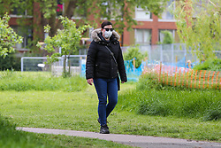© Licensed to London News Pictures. 13/05/2020. London, UK. A woman wearing face covering in a north London park as new government guidelines on the easing of the lockdown are published, allowing members of the public to spend more time in the park whilst following social distancing rules. Photo credit: Dinendra Haria/LNP