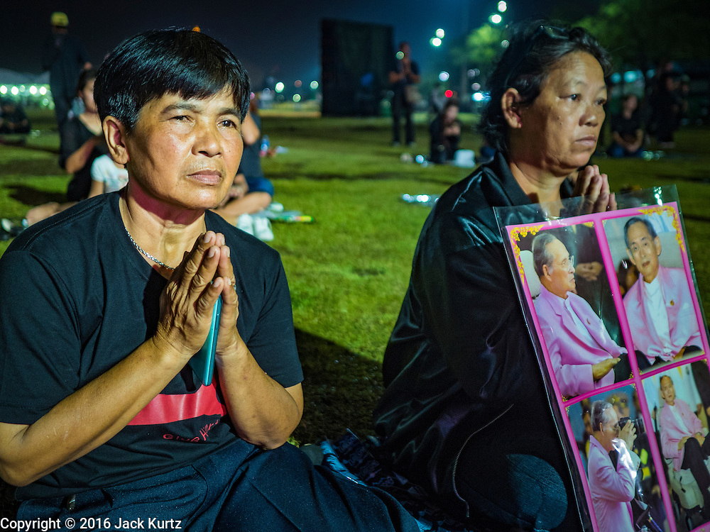 17 OCTOBER 2016 - BANGKOK, THAILAND:   Mourners with a portrait of Bhumibol Adulyadej, the late King of Thailand, gather on Sanam Luang, near the Grand Palace. Thai King Bhumibol Adulyadej died Oct. 13, 2016. He was 88. His death comes after a period of failing health. Bhumibol Adulyadej, was born in Cambridge, MA, on 5 December 1927. He was the ninth monarch of Thailand from the Chakri Dynasty and is also known as Rama IX. He became King on June 9, 1946 and served as King of Thailand for 70 years, 126 days. He was, at the time of his death, the world's longest-serving head of state and the longest-reigning monarch in Thai history.      PHOTO BY JACK KURTZ