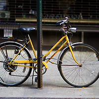 Antique looking bike locked to a street sign in New York city sidewalk.