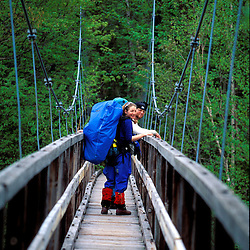 Two hikers on a foot bridge across NH's Pemigewasset River.  Mt. Liberty, White Mountains, NH