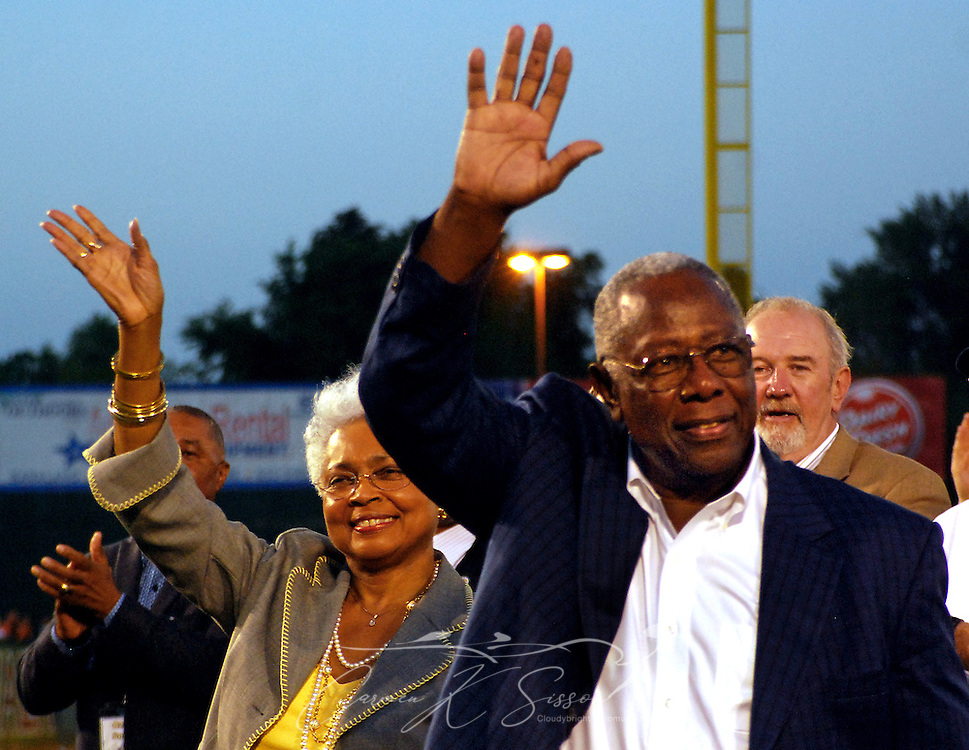 """Baseball legend Hank Aaron and his wife, Billye Aaron, wave to fans as they enter Hank Aaron Stadium for the dedication of the Hank Aaron Childhood Home and Museum April 14, 2010 in Mobile, Ala. Aaron's childhood home, originally built by his father, was relocated from the Toulminville neighborhood to the stadium's """"Gaslight Park"""" and restored in November 2008. The celebration, which included a ribbon-cutting and private reception, was attended by a star-studded roster of Hall of Famers and baseball dignitaries, including Mays, Reggie Jackson, Ozzie Smith, Bob Feller, Rickey Henderson, and Bruce Setter, along with President of Minor League Baseball Pat O'Conner, President of the National Baseball Hall of Fame Jeff Idelson, MLB Commissioner Bud Selig, and Hall of Fame senior director of exhibitions Erik Strohl. (Apex Mediawire photo by Carmen K. Sisson)"""