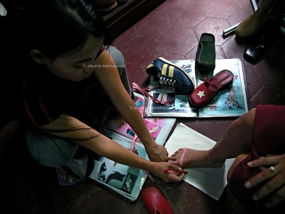 Vietnam, Hoi An:taking measures od the feet in order to make hand made shoes.