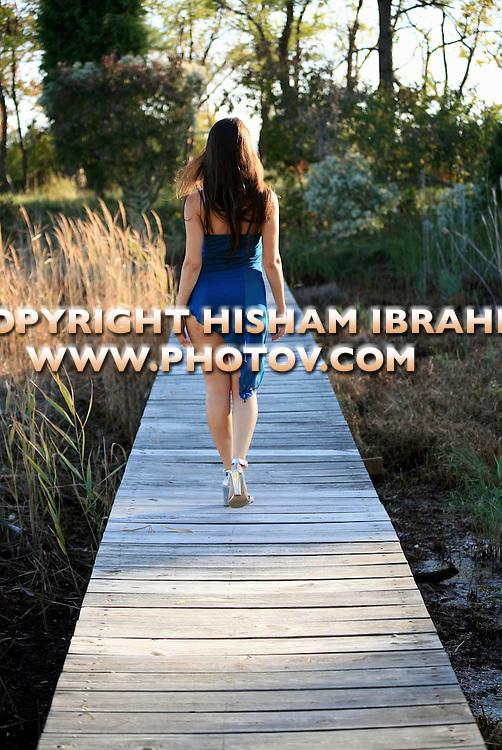Sexy woman walking alone on pier, rear view.