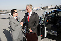 Two businessmen standing on landing strip in front of car and shaking hands.
