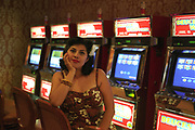 Retro 1950's girl with a flower in her hair sitting in front of slot machines, Las Vegas, USA, 2000's