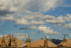 Stone roofs under puffy clouds, Cuzco, Peru, South America