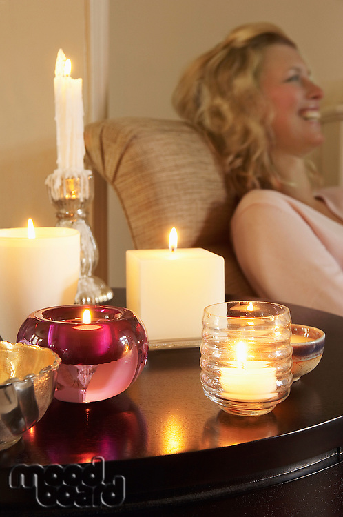 Woman Relaxing on sofa beside table with Candles side view