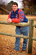 Senior picture taken in a field with young man posing in his football letter jacket from Pearce High School.