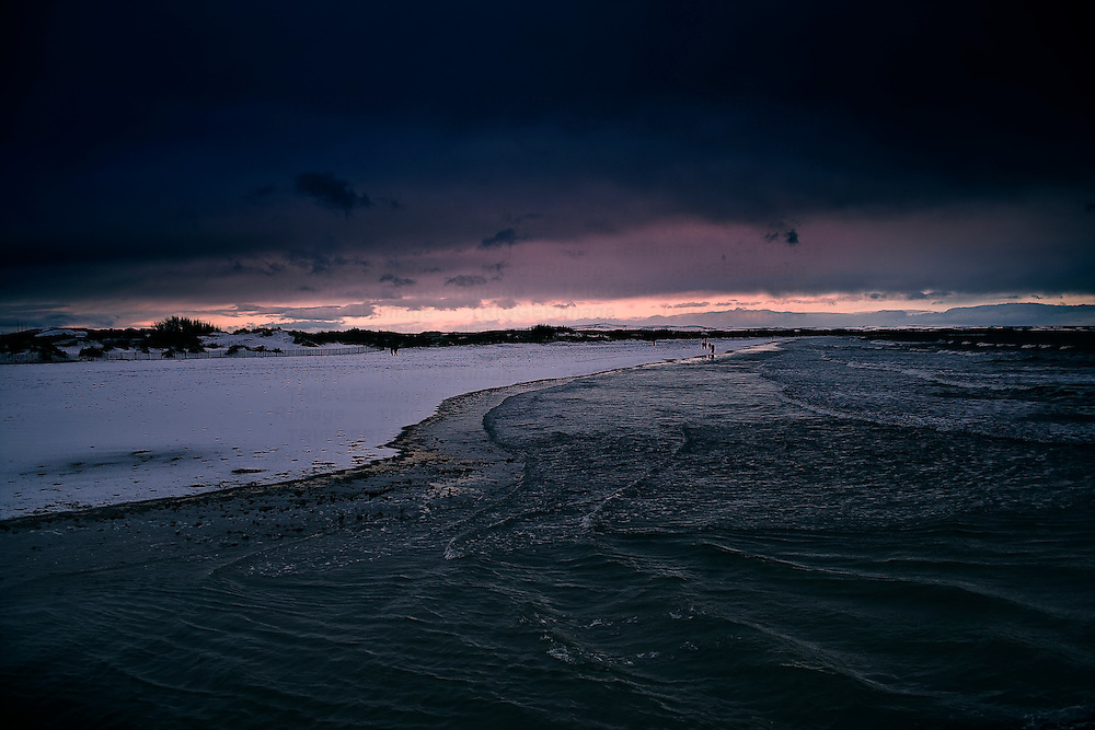 A snow covered beach at sunset.