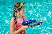 Girl plays with a water gun in a swimming pool.