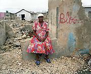 Cette femme pose devant les ruines de sa maison de?truite suite a? l'affrontement arme? de deux bandes criminelles rivales de Cite? Solei, Hai?ti. .Plus de 200 maisons ont e?te? rase?es en une journe?e dans ce bidon-ville de Port-au-Prince ou? vivent entasse?s  pre?s de 500,000 personnes.
