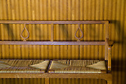 A simple wooden and rattan bench provides a place to rest in the in the foyer of the Holy Cross Chapel at Skogskyrkogården, Stockholm, Sweden.