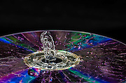 High-speed flash photograph liquid droplet. The droplet lands in the liquid and produces a coronet. the droplet is surrounded by a light reflecting CD