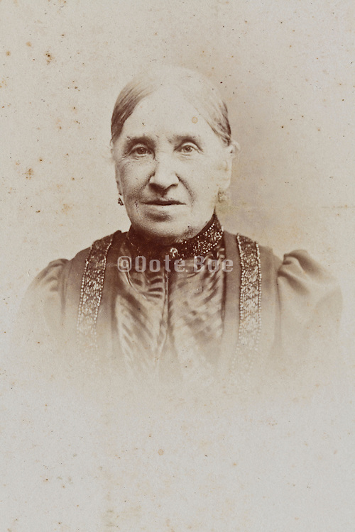 fading and damaged 1900s portrait of adult elderly woman