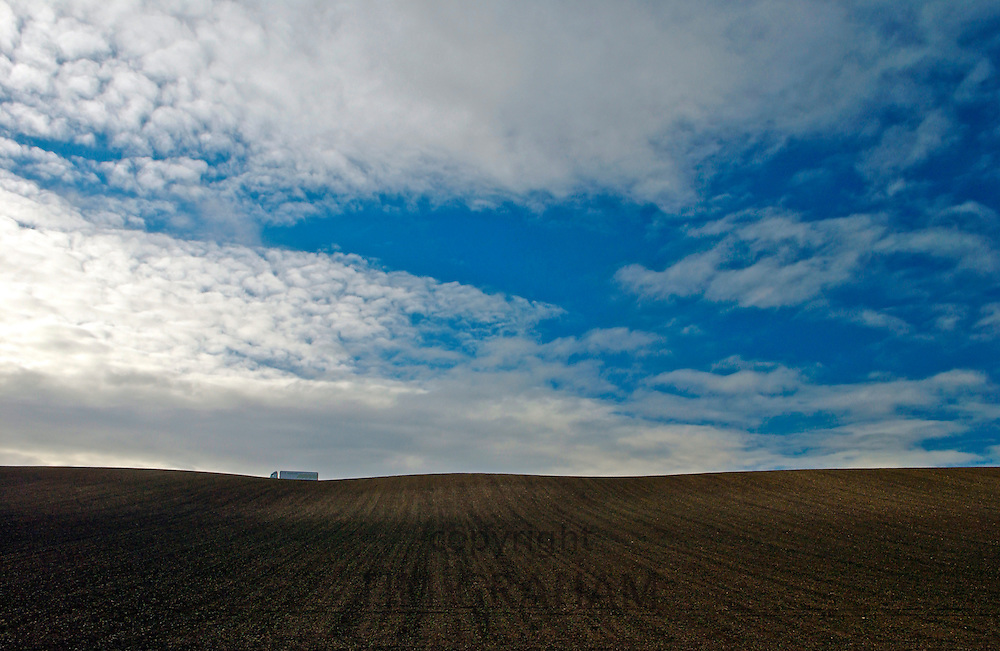 Burford ploughed field with a truck passing in the distance, Cotswolds